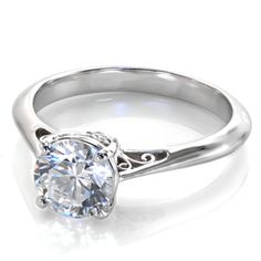 Classic Filigree - Simple, clean lines define the Classic Filigree. This solitaire features a 1.00 carat round brilliant cut diamond in a cathedral setting. The handcrafted filigree under the center stone and shoulders of the reverse tapered band give this design an artistic side-view.