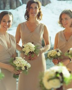 Wintry Flowers maids carried bouquets of ranunculus, tulips, pine sprigs, and small pine cones. The stems were wrapped in grosgrain ribbon with an overlay of brown sequin trim.