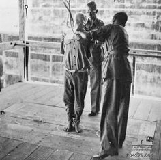 An unidentified hangman positions the noose around the neck of a Japanese war criminal as he is held steady by another unidentified British officer just prior to his execution by hanging at the gallows in Changi Gaol. The condemned man is standing, barefoot, within a circle on the trapdoor and on either side of him are two other circles indicating that the gallows had the provision for multiple simultaneous executions. 1946.