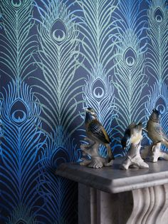 Navy wallpaper with turquoise and lime green peacock feather print with bird ornaments displayed on a marble mantelpiece. Matthew Williamson's love of colour, pattern and texture has been paired with Osborne & Little's savoir faire in furnishing fabrics and wallpaper for home interior decoration.The peacock feather has become synonymous with Matthew Williamson; first featured in the 1997 debut collection 'Electric Angels', it remains an enduring motif of the brand.