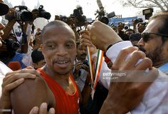 South African marathon runner, Hendrik Ramaala (L) receives a token medal from an unidentified official after winning the 42.2km Bombay International Marathon 2004 in Bombay, 15 February 2004. Some twenty thousand runners participated in the 42km marathon, a 21km half marathon and a 7km dream run running through the streets of India's financial and entertainment capital. AFP PHOTO/Rob ELLIOTT