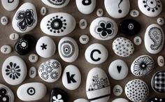 Steine bemalen schwarze Motive Blumen und Buchstaben bemalte Steine