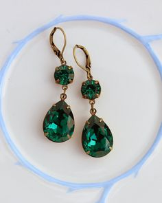 Swarovski Emerald earrings, Emerald earring, double earring, Swarovski earrings, Emerald earrings, green earrings, dangle drop earrings, Green wedding, Christmas wedding, Christmas earrings, Christmas gift, rhinestone earrings  You like green colours? There emerald colour earrings sure do flash with green. These estate style dangle earrings are made up of a new 8mm round emerald green Swarovski crystal on the top, and on the bottom is a new 18x13mm pear shaped Swarovski rhinestone. Both…