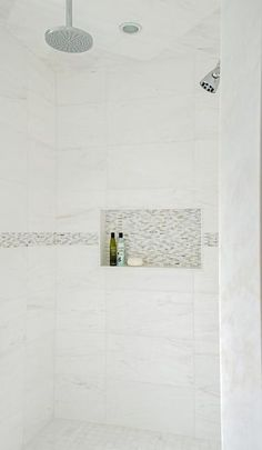 Chic walk-in shower features white marble grid tiles accented with gray mosaic border tiles fitted with a tiled niche as well as two shower heads.: