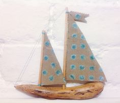 'Aqua Blue', a driftwood sailing boat, inspired by the shape of a piece found on Sweden's Baltic coast. Named for the colour of the water from whence she came.  A beautiful piece of wood, lighter than air; crackled, cracked and shaped by the waves. The knots have been eroded and smoothed.  The sturdy fabric of her sails is warmly rustic with vibrant silver/turquoise velveteen spots.  She sails dreamily on clear starlit nights when waters are calm and bright and the milky way wheels overhead.