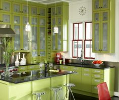 This modern, eclectic island-shaped kitchen is defined by the all-around vibrant green cabinets which contrast nicely with the dark countertops.