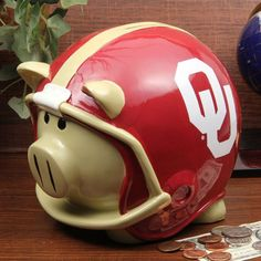 Your young Sooners fan has been saving up his loose change and dollar bills for a long time, so he can save up for a ticket to his first college football game. What better way to appreciate his devotion and his money-saving ways than with this Oklahoma-inspired Helmet piggy bank? This festive piggy features a team logo on both sides of a team-colored helmet. When your young Sooners fan is ready to break the bank and collect his money to see his team play, just pull the bottom stopper, collect th University Of Oklahoma, Oklahoma Sooners, A Team, Team Logo, College Football Games, Personalized Piggy Bank, Desk Supplies, Fan Gear, Football Helmets