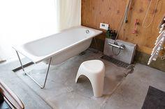 バスルームとリビングには僅かな段差があるだけ。木の壁にはFRP塗装がされているので、水濡れを気にせずシャワーを浴びられる。 モダンなバスタブは、「T-FORM」で購入したもの。
