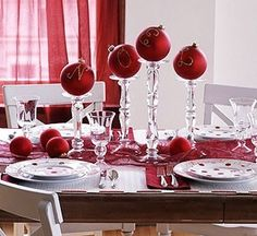 Use a gold glitter pen to spell out the word 'Noel' on red Christmas ornaments.  Then, insert them on top of long crystal candlesticks at the middle of the table.    www.flickr.com/todd kravos