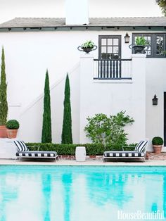 Against the white stucco, tall Italian cypresses soar like sculpture.