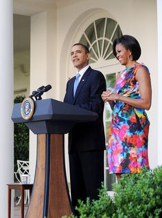 President Barack Obama delivers remarks as First Lady Michelle Obama (in Thakoon) looks on at a Cinco de Mayo reception May 5, 2010 in the Rose Garden of the White House in Washington, DC