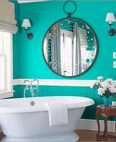 Bold turquoise bathroom with white accents. Not usually a fan of a chair rail, but the white stripe accent in this bathroom is great!