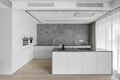 This modern kitchen showcases minimalist white cabinets, grey countertops, and a grey backsplash that covers the wall. Grey Backsplash, Grey Countertops, Floor To Ceiling Curtains, Hidden Lighting, Wood Parquet, Cocinas Kitchen, Small Hallways, Hanging Clothes, Apartment Interior