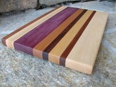 "Decorative Wood Cutting Boards by Hess. $46.99. Decorative. Handmade in the USA. Ships 2-3 Day USPS Priority Mail. Food Safe Finish. Solid Wood. This cutting board is constructed from strips Maple, Cherry, Walnut, Yellowheart, Purpleheart. It is finish sanded and four black rubber screw on feet have been added. Finished using mineral oil and a food safe natural sealer. Overall dimensions of board shown: 12"" X 7"" X 7/8"""