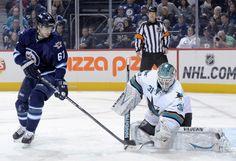 San Jose Sharks goaltender Antti Niemi makes a save as Michael Frolik of the Winnipeg Jets looks on (Nov. 10, 2013).