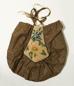 Hand-painted silk purse, possibly American, c. 1810. The purse features hand-painted velvet theorems padded with newspaper and backed with ivory silk. The theorems are outlined with ivory satin braided cord. The brown silk bag is gathered to fit around the theorems. Everything is hand stitched. The hand-painted flowers are still fresh and lovely. Theorem Painting was an American decorative technique from the first part of the 19th century. A cohesive composition is achieved through a series…