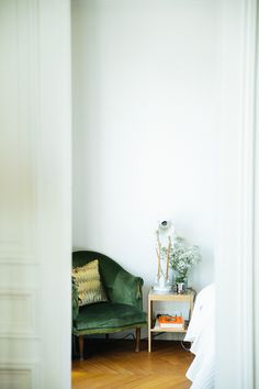 madewell et sézane, july 2015: a classic french apartment with a velvet green sitting chair and chevron wood floors.