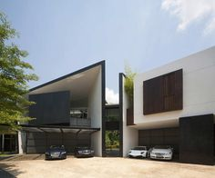 Not sure I like all the pretentious cars sitting out front, but the house itself is pretty sweet. Black & White House by Formwerkz Architects.