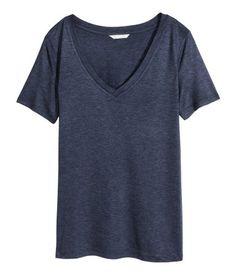 Musta. V-aukkoinen, lyhythihainen pusero kevyesti kiiltävää ja myötäilevää, ohutta trikoota.
