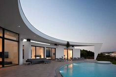 """named colunata house, this residence in lagos, portugal, overlooks a dramatic view of the atlantic ocean.  designed by portuguese architect mario martins, he describs the architecture in these words: """"The guidelines result in a set of white volumes, free and organically grouped, culminating in a semi-circular opening, which embraces the pool and opens out to the privileged sea view. the central terrace, the main space of the house, where the privacy is felt and where the horizon is…"""
