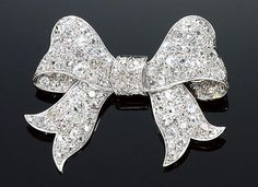 DIAMOND BROOCH, 1920S. Designed as a tied ribbon millegrain pavé-set with cushion-shaped, circular-, single- and rose-cut diamonds.