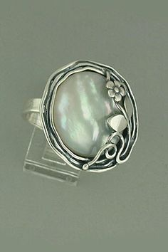Moon Bloom Ring  Hand made, sterling silver with a round mother of pearl and a bloom silver design at the top/side ring. One item only. Ring: size 8.  Size:  Price: $96.00