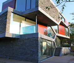 Rough grey slate and red-stained wood panels infill a zig-zagging stone frame on the exterior of a house in Venlo, the Netherlands.