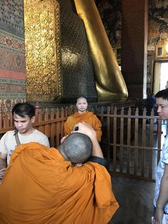 A monk photographing another monk in front of The Reclining Buddha Bangkok.