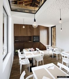 renovation of old barn ++ comac Wood floor triangulated feature wall white cafe space