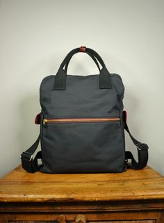 Cosmo Backpack in Black Canvas/ Men/ Messenger/ Laptop Bag/Handmade in New York/ School Bag/ Red Leather. $98.00, via Etsy.