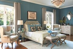 Jeff Lewis' paint color Lake.  This grey washed wood frame bed compliments a room painted in Lake. Traditionally styled benches and side chairs pair well with more modern pieces like glass lamps and metallic gold side tables in this open bedroom space.  A subtle geometric pattern in the rug adds an additional element of modern design.