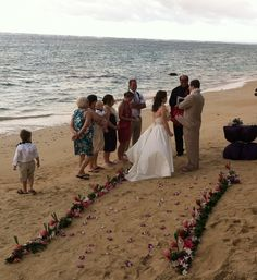 A tropical aisle of flowers in the pink and white color theme of the couple's wedding on a North Shore beach on Oahu. Aisle, photo, and wedding planning by Tori Rogers of Hawaii Weddings by Tori Rogers. www.hawaiianweddings.net