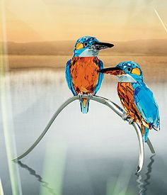 "Swarovski Blue Turquoise Kingfishers $950.00 7 1/4"" Item# 945090 A flash of blue is all you can usually glimpse of these excellent fishers. A fine detail of superb coloring features an exquisite detail on the female beak. Pair of Kingfishers in Blue Turquoise, Aquamrarine, Sun and clear crystal on silver-tone metal stand. Highly complex in production, the Kingfishers are created with approximately 20 separate parts."