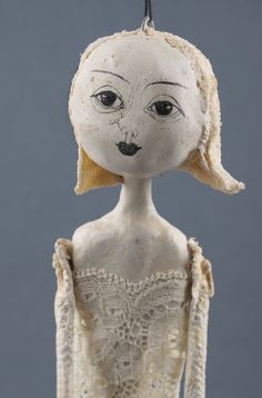 Gia is about 14 inch tall. She is made of a special clay that we made ourselves-our own formula. Her clothes are of fabric combined with a