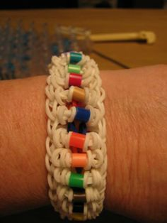 """LADDER with Perler beads. Adapted and loomed by Rose Anzulewicz on the Rainbow Loom. Rose said: """" This is a ladder Bracelet with the rubber bands wrapped 3 times around with a Perler bead in the middle. ...made with 2 looms so it goes all the way  ...just add the rubber bands and perler beads on the last rubber band going across the loom."""""""