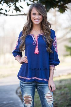 Everyone will be jealous of your look in this new blouse! Navy top with neon pink and off white design and a tassel tie in the front!