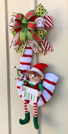 This adorable Elf is sitting on his Candy Cane waiting to greet your guests this Holiday Season. The wreath is made on a 20 inch wire frame covered in red and white chunky yarn. It features a 14 inch plush elf sitting on his candy cane holding a Wreath Crafts, Diy Wreath, Christmas Projects, Holiday Crafts, Christmas Holidays, Rustic Christmas, Christmas Parties, Elegant Christmas, Christmas Candy Crafts