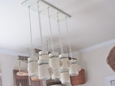 Junk Chic Cottage Laundry Room -- This was the light fixture I bought at Lowe's.  It was all black and I painted it cream and then added the light burlap and flowers to the jars.  I love that this light fixture came like this and it can also fit the vintage Ball jars.