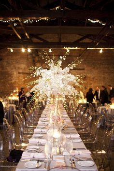 Warehouse wedding reception with ghost chairs and tall centerpieces