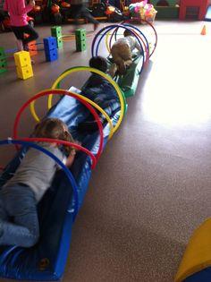 Les cerceaux ont été attachés par deux au dessus et en dessous du tapis avec de grands Rilsans. Du coup quand les enfants passent a l'intérieur, il y a un effet de bascule de gauche à droite