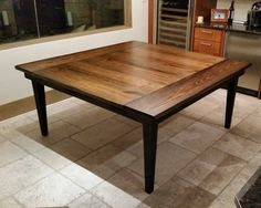 """66""""x66"""" Square Farmhouse Table with tapered legs, jointed top, and endcaps stained in Dark Walnut with a Satin Sheen and Black painted base."""