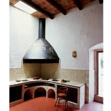 Although somewhat austere, the cocina (kitchen) is enlivened with crimson floor tiles. Traditional decorative tilework embellishes the counter, backsplash and walls.