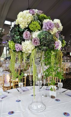 This stunning tall centerpiece filled with pops of purple, white and green was perfect for a wedding we planned at The Ashford Estate and would look amazing at an outdoor rehearsal dinner too!