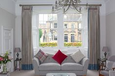 Inspiration for dressing traditional sash windows.  Install a pole across the front of the window recess.  Silk curtains with contrast borders at a traditional Edinburgh window by Catherine Lepreux Interiors