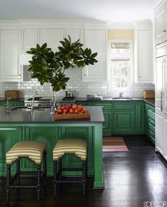 In this contemporary Houston home designed by J. Randall Powers, the kitchen's lower custom cabinets are painted deep green in a strié effect. The sink fittings are by Rohl and the range is by Wolf, while the refrigerator is by Sub-Zero. The stools are by Mecox and the wall tiles are by Walker Zanger.