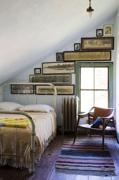 attic bedroom with a brilliant use of art. All of the long framed images draw you in and make you less aware of slanted wall/ceiling.