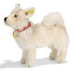 A STEIFF STANDING LAIKA THE SPACE DOG, (1325,0), white mohair, brown, black and white glass eyes, black stitching, red collar, inoperative squeaker, script button, yellow cloth tag and chest tag, 1958 --10½in. (26.5cm.) long