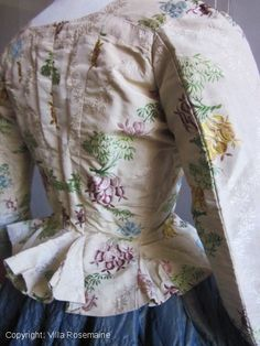 """Caraco/bodice (rear view), 1780s, France, damask silk earlier date (Louis XV) Lyon or Spitafields. Probably hand re sewn during reign of Louis XVI. Superb cream damask brocaded with glycines bouquets and pomegranates in gold, purple and blue sky tones. Linen lining corseted front with eyelets for lacing (instead of the rigid bodice!). Pekin silk re-used for the V back and light green chiffon silk for the lining of the sleeves. Basques and """"Pet en l'air"""" at the back waist. Photo villa-rosemaine"""