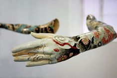 The arms were cast in porcelain from a professional ballerina, which are painted with Japanese Yakuza-style tattoo patterns.