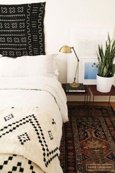 That bedroom has an ethnic inspiration brought the persian rug on a floor and a geometric pattern on the cover sheet. the black and white colors definitely add a chic note to the room.